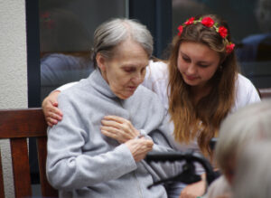 care home workers - girl taking care of woman